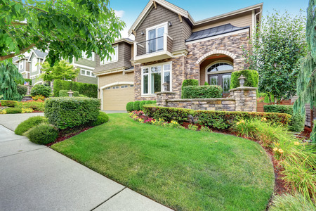 Beautiful curb appeal of American house with stone trim and perfectly trimmed shrubs. Northwest, USA