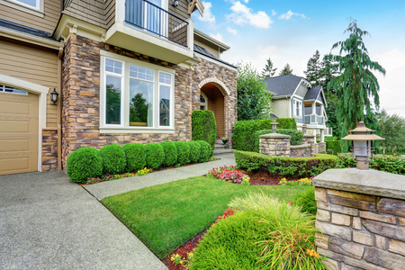 curb: Beautiful curb appeal of American house with stone trim and perfectly trimmed shrubs. Northwest, USA Stock Photo