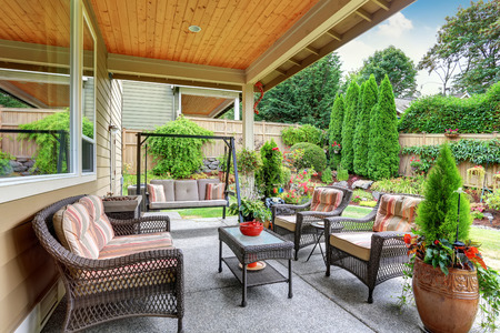 Cozy covered sitting area with wicker chairs and swing bench. Northwest, USA Stock Photo