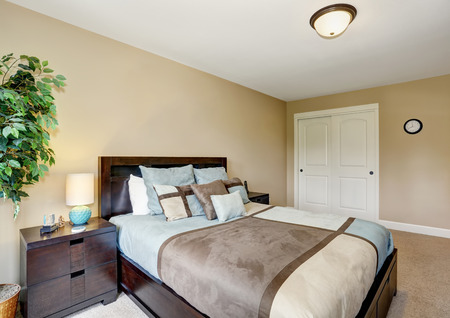 king size bed: King size bed with blue and brown bedding. Bedroom interior. Northwest, USA