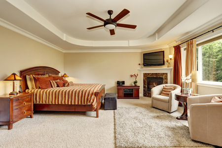 Master bedroom interior with corner fireplace and king size wooden bed. Northwest, USA