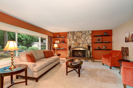 stone fireplace: Cozy family room in red tones with stone fireplace and some shelves. Northwest, USA