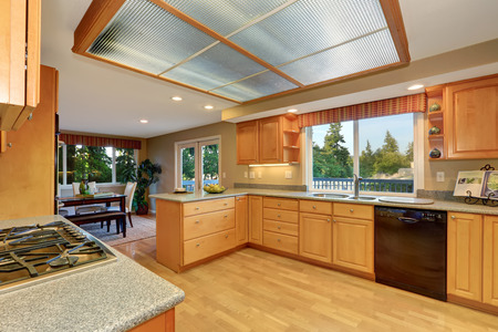 skylights: Bright wooden kitchen interior with skylight and hardwood floor. Dining room view. Northwest, USA