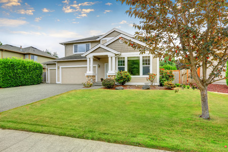 Neat beige home with two garage spaces and well kept front garden. Northwest, USA
