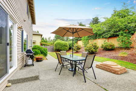 Patio table set with umbrella in the back yard. Northwest, USA