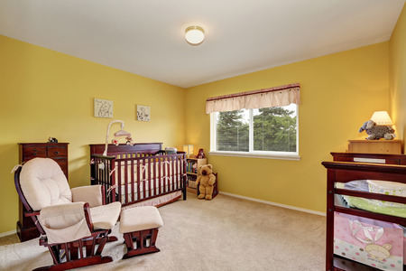 rocking chair: Cute yellow nursery room with comfortable rocking chair . Northwest, USA
