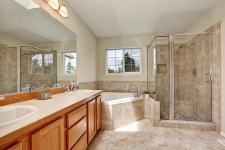 Baño principal con bañera de esquina, claraboya y suelos de baldosas. Noroeste, EE.UU. Foto de archivo