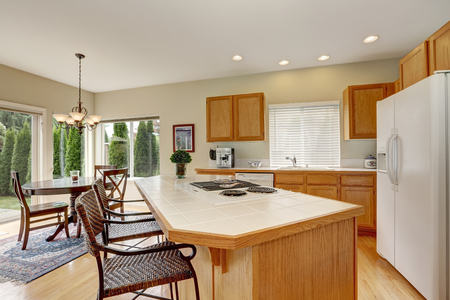 stools: Light wooden kitchen interior with kitchen island and wicker stools. View of dining table set. Northwest, USA