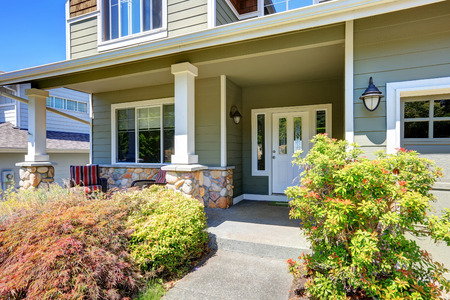 home exterior: Covered porch with white columns and stone trim. Northwest, USA Stock Photo