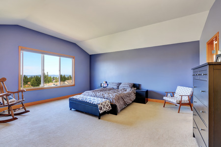 vaulted ceiling: Spacious blue bedroom with vaulted ceiling. Furnished with rocking chair, black chest of drawers and bed with bench. Northwest, USA Stock Photo