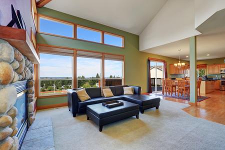 Voutée salon de plafond avec cuir noir canapé, cheminée en pierre et mur vert. Northwest, États-Unis
