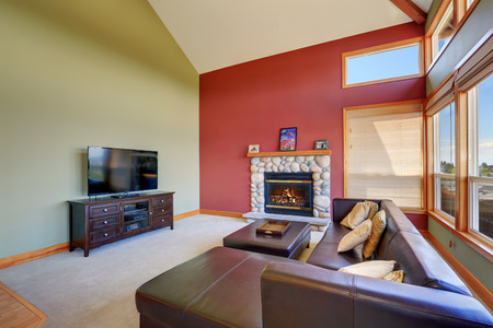 set in stone: Vaulted ceiling living room with black leather sofa set, stone fireplace and red contrast wall. Northwest, USA