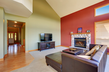 stone fireplace: Vaulted ceiling living room with black leather sofa set, stone fireplace and red contrast wall. Northwest, USA