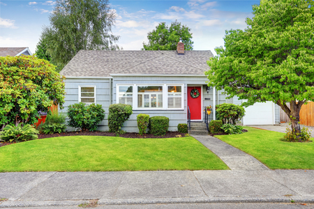 Exterior of small American house with blue paint and red entrance door. Northwest, USA Stock Photo
