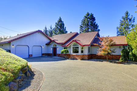 curb appeal: Curb appeal of blue house with brick trim and double doors garage. Northwest, USA