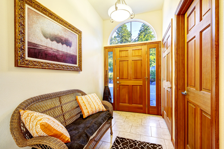 tile flooring: Bright hallway with wicker sofa and orange pillows. Tile flooring and wooden front door. Northwest, USA Stock Photo