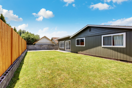 northwest: Back yard house exterior with wooden fence and well kept lawn around. Northwest, USA Stock Photo