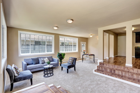 Hallway interior in beige walls. Living room with modern blue sofa and armchair. Northwest, USA Stock Photo