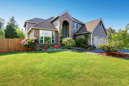 Luxusní dům exteriér s cihlou a vlečky lemováním a dvojgaráží. Dobře udržovaná zahrada kolem. Severozápad, USA Reklamní fotografie