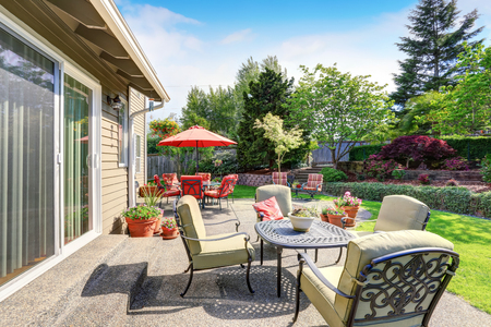 garden furniture: Well kept garden at backyard with concrete floor patio area and opened red umbrella. Northwest, USA Stock Photo