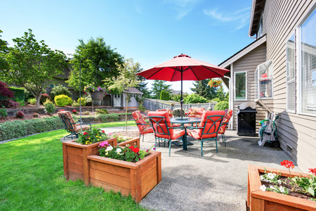 home garden: Well kept garden at backyard with concrete floor patio area and opened red umbrella. Northwest, USA Stock Photo