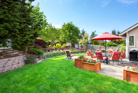 northwest: Well kept garden at backyard with concrete floor patio area and opened red umbrella. Northwest, USA Stock Photo