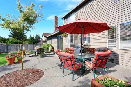 Well kept garden at backyard with concrete floor patio area and opened red umbrella. Northwest, USA Stock Photo