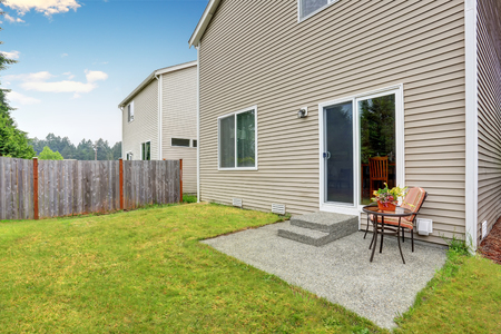 Fenced backyard with small patio area. Well kept lawn around. Northwest, USA Stock Photo