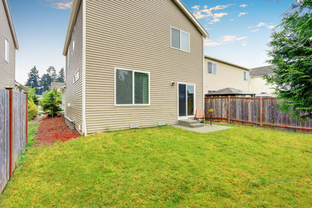 lawn area: Fenced backyard with small patio area. Well kept lawn around. Northwest, USA Stock Photo