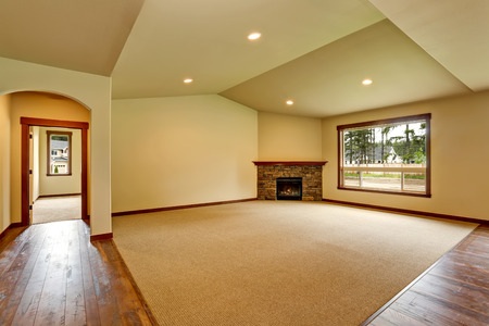 open floor plan: Open floor plan. Empty living room with fireplace, and carpet floor. Connected to kitchen area. Northwest, USA Stock Photo
