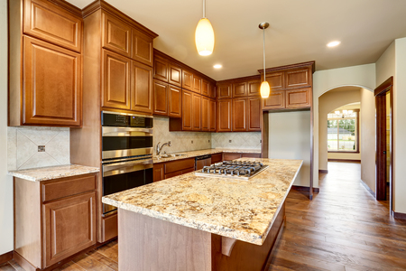 cabinets: Kitchen room interior with wooden cabinets with granite counter top and island. Northwest, USA