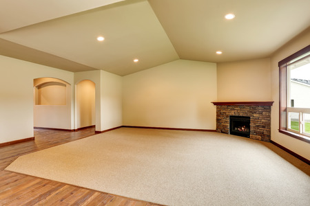Open floor plan. Empty living room with fireplace, and carpet floor. Connected to kitchen area. Northwest, USA Stock Photo