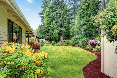 Well kept garden at backyard with trees, bushes and flowers. Northwest, USA Stock Photo