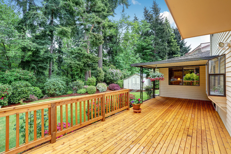 Wooden walkout deck. Well kept garden with bushes and flowers. Northwest, USA Banco de Imagens