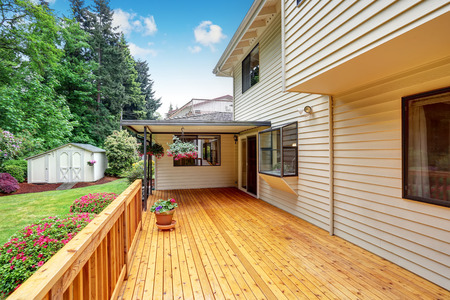 Wooden walkout deck. Well kept garden with bushes and flowers. Northwest, USA Stock Photo