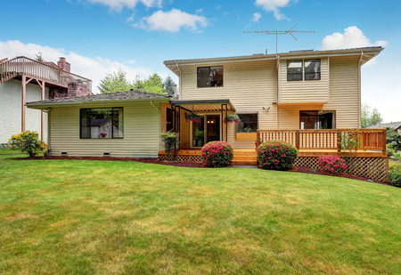 home and garden: Wooden walkout deck. Well kept garden with bushes and flowers. Northwest, USA Stock Photo