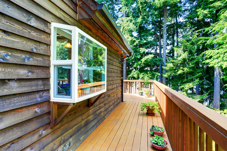 wooden railings: Balcony house exterior with wooden trim and flowers pots. Also wooden railings. Northwest, USA