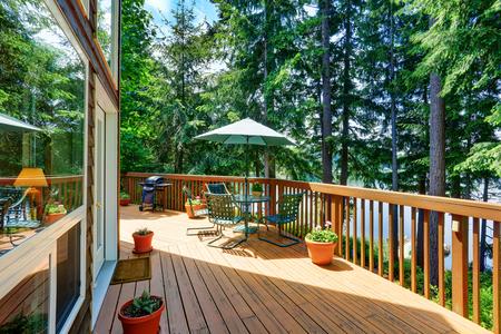 Balkon huis buitenkant met patio en opende groene paraplu. Ook houten leuningen en bloemen potten. Northwest, USA