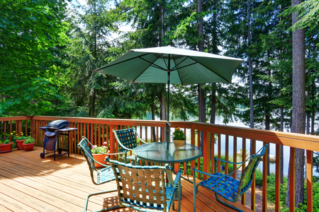 balcony: Balcony house exterior with patio area and opened green umbrella. Also wooden railings and flowers pots. Northwest, USA