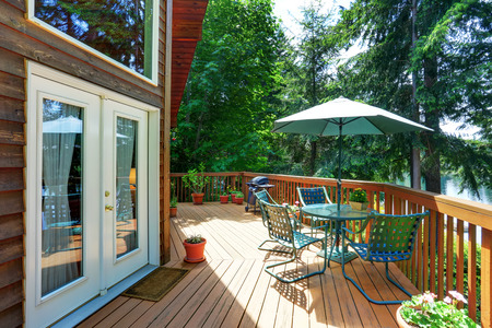 wooden railings: Balcony house exterior with patio area and opened green umbrella. Also wooden railings and flowers pots. Northwest, USA