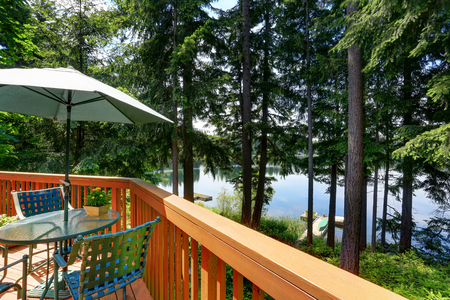 waterfront: Waterfront lake with small pier. View from balcony with patio area. Northwest, USA Stock Photo