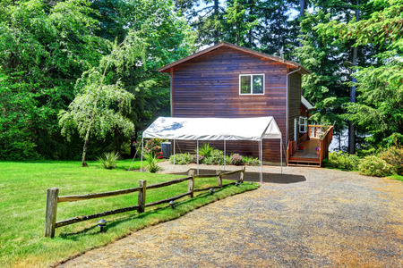 Backyard house exterior with wooden trim and small marquee and well kept lawn. Northwest, USA