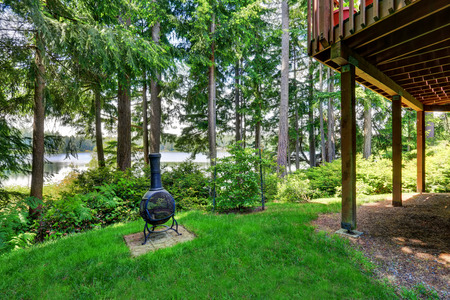 Backyard house exterior with wooden trim and well kept lawn. Perfect water view. Northwest, USA