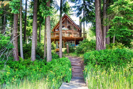 House exterior with wooden trim and large balcony. Trees around. View from small pier. Northwest, USA