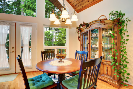 Traditional dining area interior with wooden table set and hardwood floor. Open floor plan. Northwest, USA