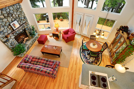 Open floor plan living room interior with rocks trim fireplace and big windows. Also dining area. Top view. Northwest, USA Stock Photo