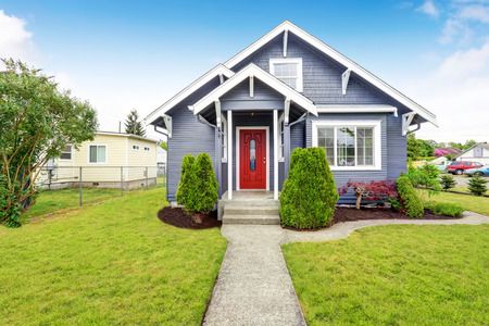 Classic American house exterior with siding trim, red entry door and concrete floor porch. Northwest, USA