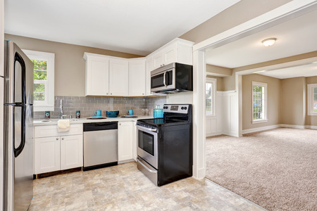 cabinets: Kitchen room interior with white cabinets and tile floor. Northwest, USA Stock Photo