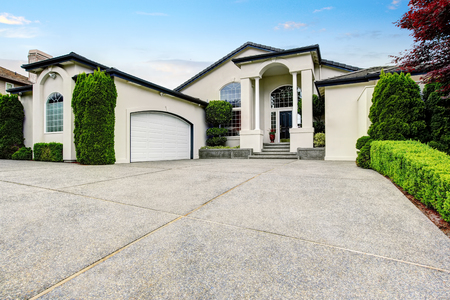 curb appeal: Luxury house exterior with concrete floor porch with columns, big garage and nice landscape desing. Northwest, USA