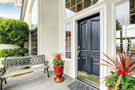 Casa de lujo de entrada salida al exterior con porche con columnas de suelo de cemento. También el banco en el porche. Noroeste, EE.UU.